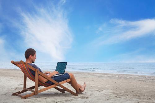 Unabhängig am Strand mit Laptop